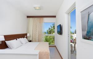 A bed or beds in a room at Mar Brasil Hotel