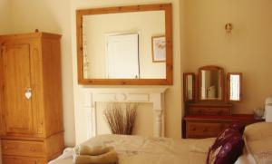 A bed or beds in a room at Harlequin Guest House with parking