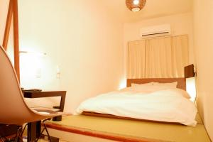 A bed or beds in a room at Hotel&Co. Sagami