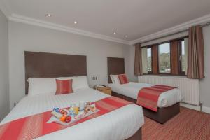 A bed or beds in a room at Best Western Bradford Guide Post Hotel