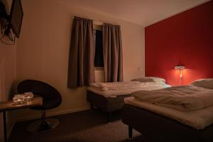A bed or beds in a room at Skagi Senja hotel & lodge