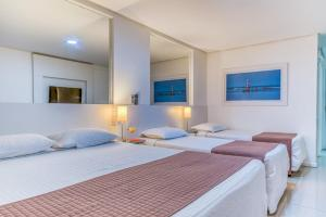 A bed or beds in a room at Hotel Brisa Praia