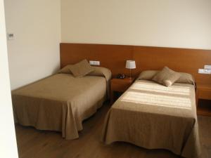 A bed or beds in a room at Pensión Residencial Platas