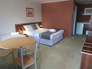 A bed or beds in a room at Junction Motel Wagga