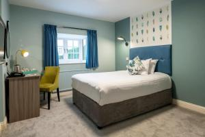 A bed or beds in a room at Wisteria Hotel