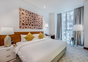A bed or beds in a room at Grand Mercure Hotel and Residences Dubai Airport
