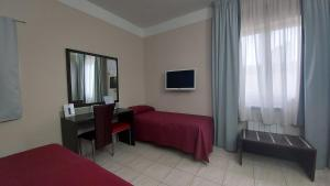 A bed or beds in a room at Idria Hotel