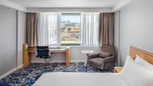 A bed or beds in a room at Crowne Plaza Sydney Coogee Beach