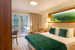 A bed or beds in a room at Hotel Verde Montana Wellness & Spa