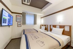 A bed or beds in a room at Hotel Emit Shibuya