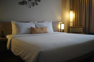 A bed or beds in a room at Grand Zuri Cikarang Jababeka
