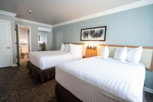 A bed or beds in a room at Alexis Park All Suite Resort