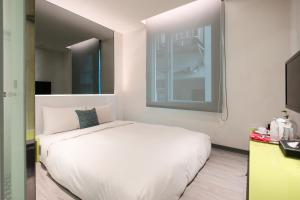 A bed or beds in a room at CityInn Hotel Plus - Taichung Station Branch