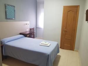 A bed or beds in a room at Hostal Soto