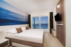 A bed or beds in a room at Bluesun hotel Neptun - All inclusive
