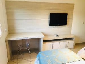 A television and/or entertainment centre at Apartamento Encantador, duas suítes vista mata