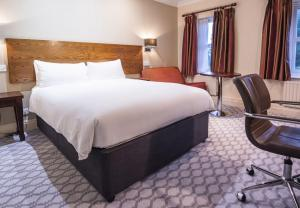 A bed or beds in a room at Hilton Avisford Park