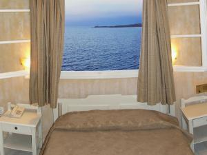 A bed or beds in a room at Pandrossos Hotel