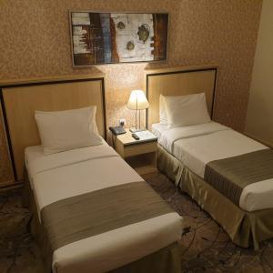 سرير أو أسرّة في غرفة في فندق الماسة مكة