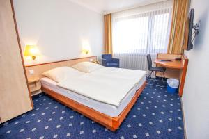 Ein Bett oder Betten in einem Zimmer der Unterkunft Hotel Heldt Dependance