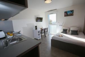 A kitchen or kitchenette at All Suites Bordeaux Pessac