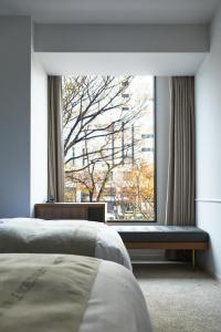 A bed or beds in a room at The Knot Hiroshima
