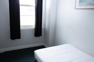 A bed or beds in a room at Grand Hotel Rockdale