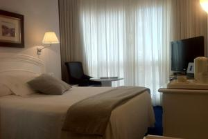 A bed or beds in a room at Sercotel Las Rocas