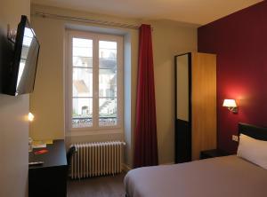 A bed or beds in a room at Hôtel Le Dormeux