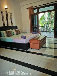 A bed or beds in a room at Serendib Village Guest House