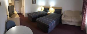 A bed or beds in a room at Cooma Motor Lodge Motel