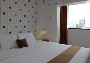 A bed or beds in a room at Inkari Suites Hotel