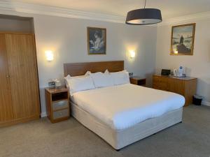 A bed or beds in a room at Legends Hotel