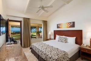A bed or beds in a room at Hotel Tamarindo Diria Beach Resort