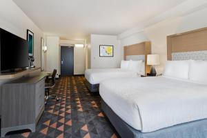 A bed or beds in a room at Holiday Inn & Suites Across From Universal Orlando