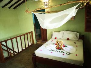 A bed or beds in a room at Demani Lodge Zanzibar