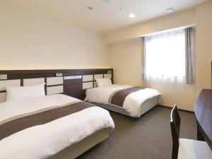 A bed or beds in a room at Urban Hotel Minami Kusatsu