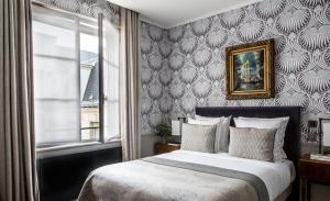A bed or beds in a room at Hotel Des Saints Peres - Esprit de France