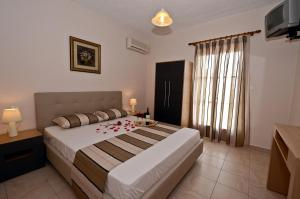 A bed or beds in a room at Oasis Deluxe Apartments