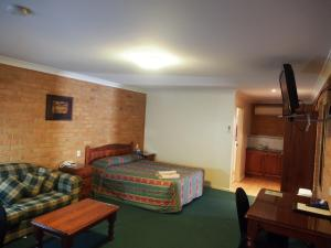 A bed or beds in a room at Cobar Town & Country Motor Inn