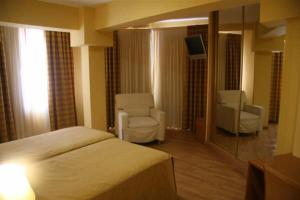 A bed or beds in a room at Hotel Leyton