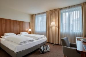 A bed or beds in a room at Das Triest Hotel