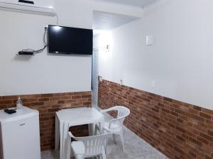 Una televisión o centro de entretenimiento en Suítes Meia Lua