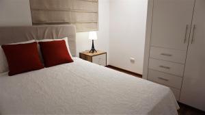 A bed or beds in a room at APARTAMENTO cerca al Aeropuerto Lima - Pe