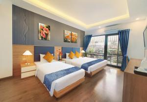A bed or beds in a room at Amorita Boutique Hotel Hanoi