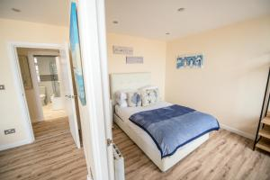 A bed or beds in a room at Beachfront sea-view apartments, peaceful & tranquil coastal escape, central location, 1 minute to the beach, uninterrupted sunset views, managed by Buoy and Oyster