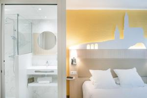 A bed or beds in a room at Hôtel Saint Sauveur