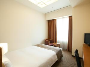 A bed or beds in a room at KKR Hotel Umeda