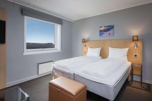 A bed or beds in a room at Scandic Vestfjord Lofoten