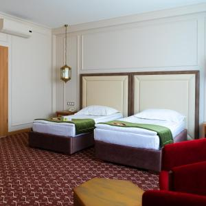 A bed or beds in a room at Jumbaktas Astana Hotel